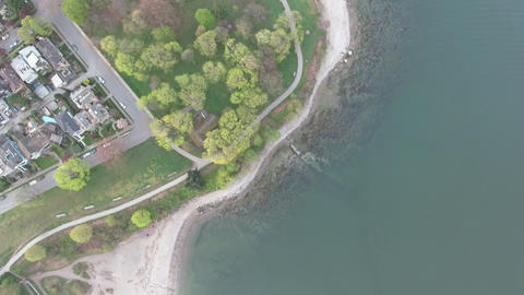Aerial view of beach and ocean near a residential area with a small park Live Action