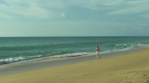Healthy, Young, Woman Runs Along The Beach Footage