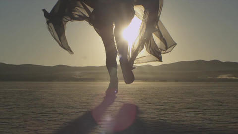 Girl with a fabric runs towards sunset in the desert. Young woman running toward Footage