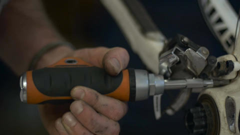 A man disassembles a rear derailleur on a bicycle with a screwdriver. The screw