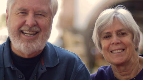 An attractive elderly couple with gray hair smiling and laughing outside. The ba Footage