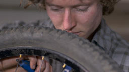 A handsome millennial man works on a mountain bike with an allen wrench and tire Footage