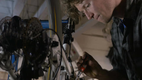 A millennial bicycle mechanic makes minor adjustments to a mountain bike with a  Footage