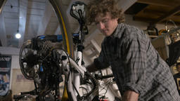 Low angle of a bicycle mechanic adjusting the gears on a mountain bike on a stan Footage