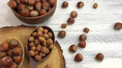 Hazelnuts in a bowl near a spoon peeled walnut Footage