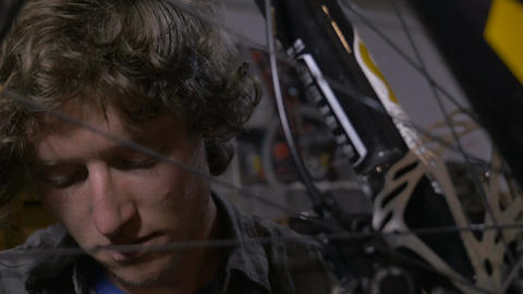 Handheld shot of a young man working on a bicycle shot through the spokes of a m Footage