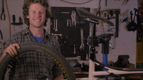An attractive millennial man stands next to a bicycle in his workshop and smiles Footage