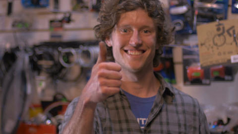 A handsome millennial small business owner smiles and gives a thumbs up in his r Footage