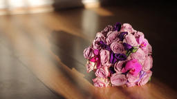 Bridal bouquet sitting on a brown wooden table waiting to be taken to church 76 Footage