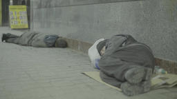 Two beggars, the homeless lying on the floor of the underpass Footage