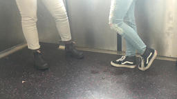Legs of teens wearing ripped and white jeans on the train ビデオ