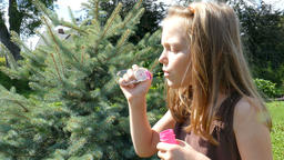 Girl is blowing soap bubbles Footage