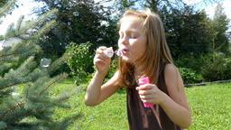 Little happy girl blowing soap bubbles Footage