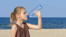 Young girl is drinking water on a beach in a hot summer day ビデオ