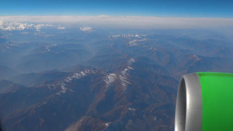 Beautiful view through airplane window, airplane flying above the clouds and mou Footage