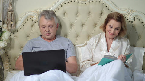 Senior couple relaxing in bed with laptop and book Live Action