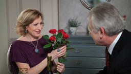 Happy elderly lady receiving flowers from man Footage