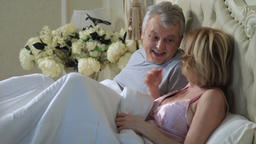 Mature loving couple lounging in bed after awaking Footage