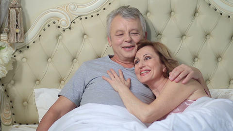 Couple lounging in bed after awaking cuddling Footage