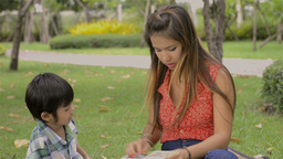 Asian Mother and Son Reading Together in a Park - Tracking Shot Footage