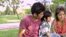 Young Asian Parents Teaching Son to Read - Dolly Shot Stock Video Footage