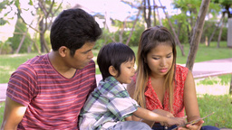 Young Asian Parents Teaching Son to Read - Dolly Shot Footage