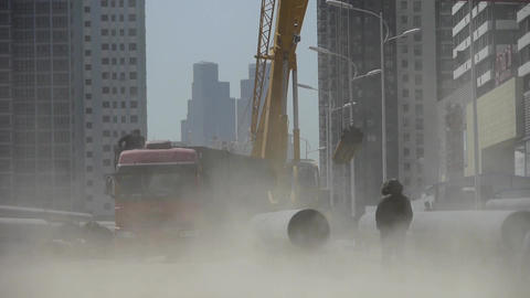 Crane lifting pipes in Construction site,sandstorm Footage