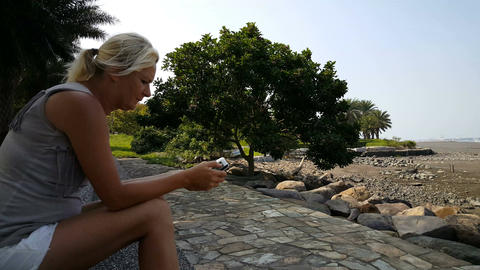 Blond woman playing with mobile phone at waterfront Footage