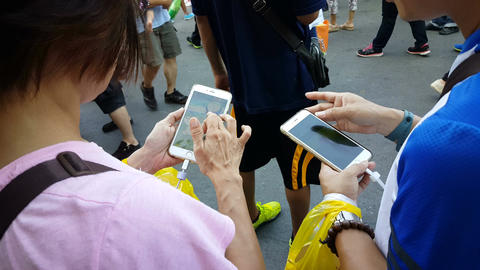 Woman playing Pokemon Go on mobile phone ビデオ