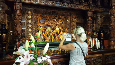 Blonde woman takes pictures of temple furniture Footage