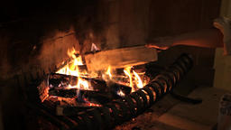 Woman Stacks Pieces Of Wood In A Fireplace With Burning Wood And Flames Live Action