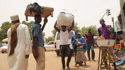 Niger, Africa. July 2013. Marketplace with men carrying goods on their heads Footage