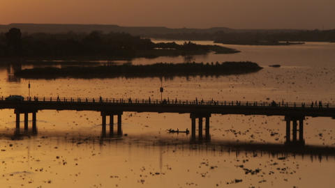 Beautiful african golden sunset by the Niger river with bridge and boats Footage