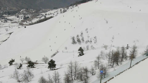 View over the ski slopes and facilities of chairlift up the mountain slopes cove Footage