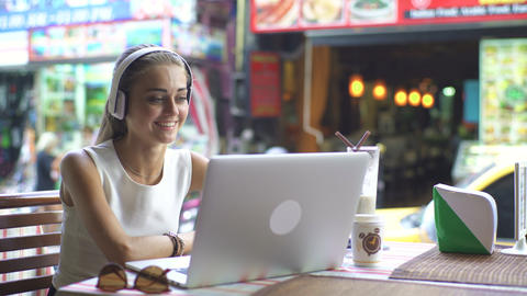 Young Woman Using Heaphones And Laptop For Video Chat Footage
