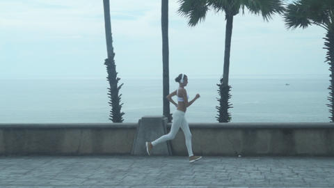 Young Woman Running Along The Embankment Footage