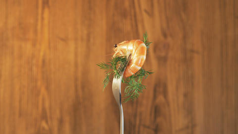 Rotating Fork With Prawn on Wooden Background Footage