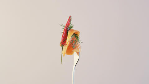 Rotating Fork With Salmon and Chili Pepper on Almond Background Live Action