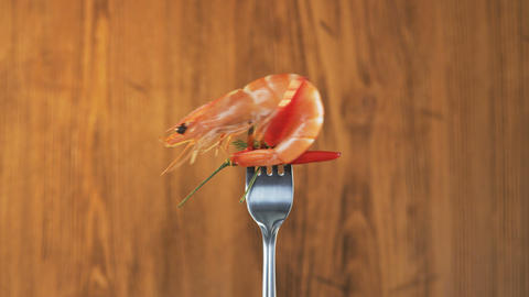Rotating Fork With Prawn and Chili Pepper on Wooden Background Footage