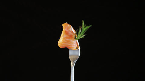 Rotating Fork With Salmon and Rosemary on Black Background Live Action