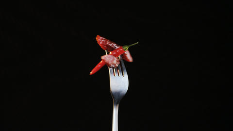 Rotating Fork With Two Sausages and Chili Pepper on Black Background Footage