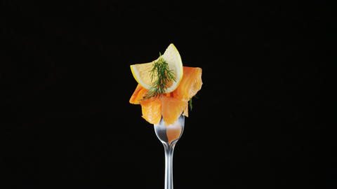 Rotating Fork With Salmon and Lemon on Black Background Footage