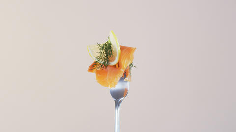 Rotating Fork With Salmon and Lemon on Almond Background Stock Video Footage