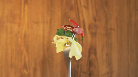 Rotating Fork With Sausage and Cheese on Wooden Background Live Action