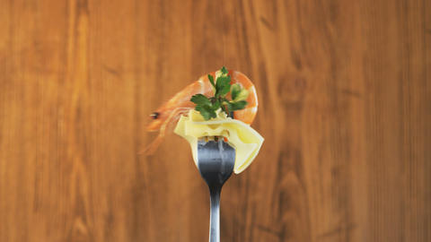 Rotating Fork With Prawn and Cheese on Wooden Background Footage