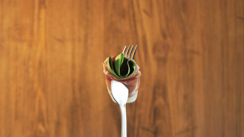Fork With Ham and Lettuce on Wooden Background Footage