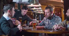Bartender bringing beer glass client pub bar 4k video. Men friends drinks lager Footage