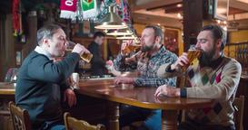 Friends group talks drinks beer at pub bar 4k video. Men taste lager cheers Footage