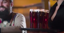 Waiter girl brings beer glasses men 4k video pub bar. Male friends having fun Footage