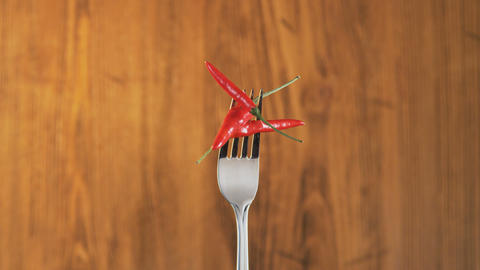 Fork With Three Chili Peppers on Wooden Background Footage